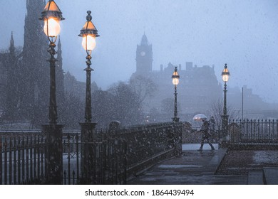 Edinburgh, United Kingdom - January 16 2018: A winter storm of snow flurries in Edinburgh, Scotland disrupts a commuter with an umbrella in front of the Walter Scott Monument and Waverley Station.