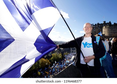 EDINBURGH,UK - OCTOBER 6, 2018: Kenneth Lowe, a Network Rail engineer, holds aloft a saltire from the Edinburgh Castle Esplanade as campaigners for Scottish independence march through the city
