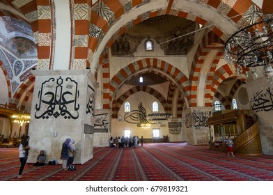 Edirne, Turkey - July 7, 2012: Interior of the Old Mosque. Paintings, arabic inscriptions and praying muslims.