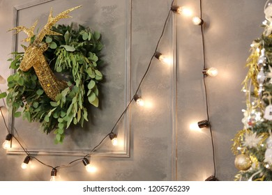 Edison bulb lamps and deer's head on the dark grey wall in the Christmas decorated room