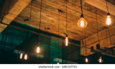 Edison bulbs dangle from the wooden ceiling with green light in the background.