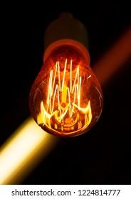 Edison lamp design on a dark background. Edison diode bulb. Glowing Edison bulb spiral on a black blurred background. Designer interior light.