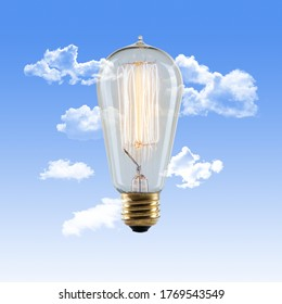 Edison Lightbulb with Glowing Filament on a Sky Blue Background with Clouds
