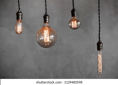 Edison retro lamp Incandescent bulbs on gray plaster wall background in cafe. Concept idea