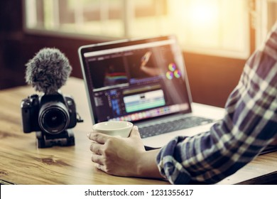 Editor freelance use laptop editing video and holding coffee cup in working time in house studio