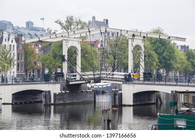 Editorial: AMSTERDAM, NETHERLANDS, September 23, 2018 - The Skinny Bridge with a lonely pedestrian early in the morning