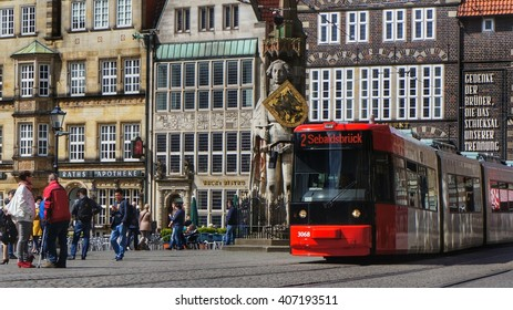 Editorial: Bremen, Germany, 17th April 2016. Tram trolley of the local company for public transportation passing the market square with the famous statue of 'Roland von Bremen' ('Roland of Bremen')