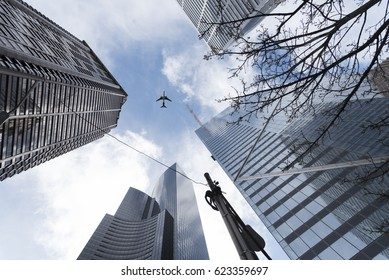 Editorial building and landmarks photography, downtown Seattle looking up at airplane flying above skyscrapers on sunny spring day circa April 2017