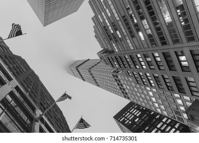 Editorial buildings and landmarks in New York City on overcast day looking up at skyscrapers reaching into the sky circa January twenty seventeen winter in black and white.