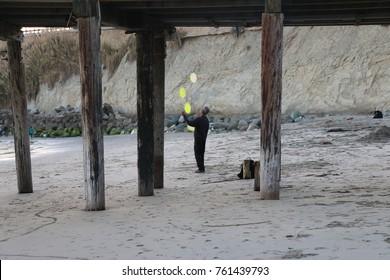Editorial.  Capitola Beach, California, USA.  11/5/2017.  Man juggles frisbees under the Capitola Wharf at sunset.