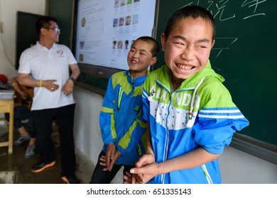 Editorial GanSu, China - May 17, 2017: Our volunteers are singing children, the two male students are invited to sing together, they are still very shy.