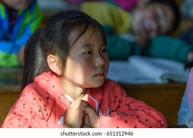 Editorial GanSu, China - May 18, 2017:Rural children in class, window sunshine into classroom, girl serious lectures.
