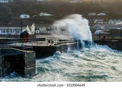 Editorial: Houses and potential trademarks. Portreath, Cornwall, UK, 01/16/2018 the Inner Harbour Wall Gets Battered by a Deep Atlantic Swell