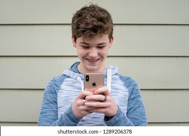 Editorial January 19, 2019 Teenage boy texting on his Apple iPhone x