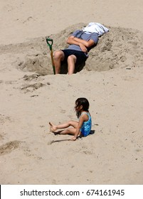 EDITORIAL.  Jul 2, 2017.  Capitola, CA.  Man at the beach with towel around his head after digging a hole; a small child sits nearby.