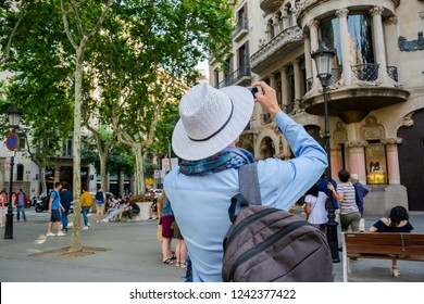Editorial. May, 2018. Barselona, Spain. A young man, tourist with a backpack and in a hat and takes photos by smartphone in front of a historic building in the center of Barcelona