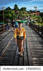 Editorial Mon ethnic woman walking and carrying stuffs on her head at the bridge in Sangklaburi Kanchanaburi Thailand on 29 September 2017