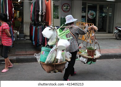 Editorial: Old Woman Carries Baskets of Produce to Sell on Kao San Road, Central Bangkok, on 13th October 2013.