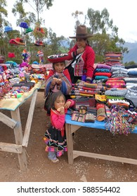 Editorial photo of Peruvian mother and her children dress in traditional costume with exotic hat selling handicraft goods at side street market in Peru ,South America,Andes mountain,January 2017