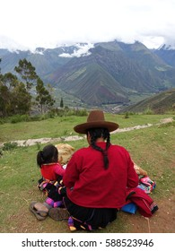 Editorial photo,Mother and child,Peruvian woman with hat and pigtail hair style,a daughter,Andes mountain background,cloudy sky,Peru,South America,summer 2017