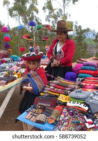 Editorial photo,Peruvian mother and daughter dress in traditional costume with hat ,selling handicraft at local side street Indian market,Peru,South America with Andes mountain background.January 2017