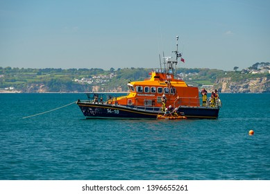 Editorial: RNLI, Unknown members of the public, Logos. Polkerris, Cornwall UK, 11/05/2019. Fowey Harbours resident lifeboat pulls into the popular recreational semi harbour at Polkerris for a PR event