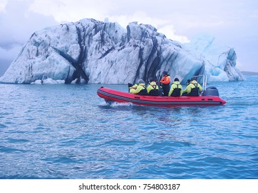 Editorial shot of tourists on glacier boat tour close to large iceberg in Jökulsárlón lake, Iceland on 25 September 2017
