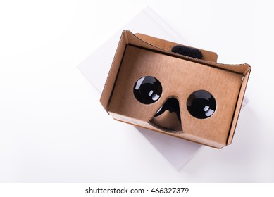 editorial shot for virtual reality headset by Google, assembled from pre-cut cardboard and bi-convex lenses. isolated over a white background on a white book. Taken on July, 2016.