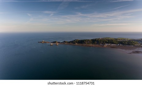 Editorial SWANSEA, UK - JUNE 22, 2018: The coastline along Mumbles showing Mumbles Lighthouse and the newly refurbished Mumbles Pier in Swansea, South Wales, UK