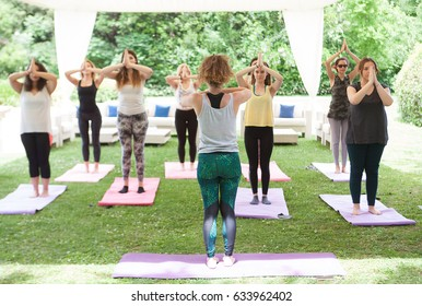 """""""Editorial use only"""" the back of a yoga teacher, teaching yoga with the students in Votanikos garden in Athens. Athens. Greece, May 03 - 2017.""""Editorial use only"""""""