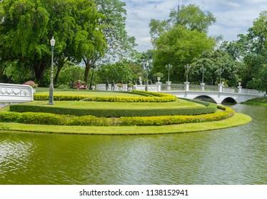 Editorial use only; beautiful manicured shrub garden with  pond and bridge, taken at Ayutthaya, Thailand, taken in July, 2018.