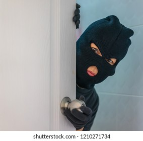 Editorial use only; a burglar in a balaclava mask, is breaking into a house, taken at Bangkok, Thailand, in September, 2018.