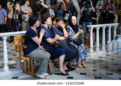 Editorial use only. Burial service in a church: relatives sit on a bench dressed in mourning clothes and crying for the late, crowd of people in a background. August 10, 2017. Kiev, Ukraine