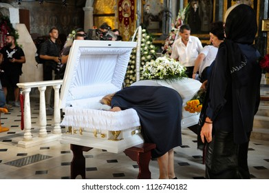 Editorial use only. Burial service: woman kissing the late in a coffing giving her last farewell. August 10, 2017. Kiev, Ukraine
