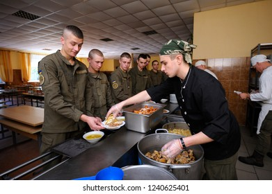 Editorial use only. At a chow hall: soldiers standing in front of a serving counter for meal, kitchen worker distributing food from pots. November 12, 2018. Novo-Petrivtsi military base, Ukraine