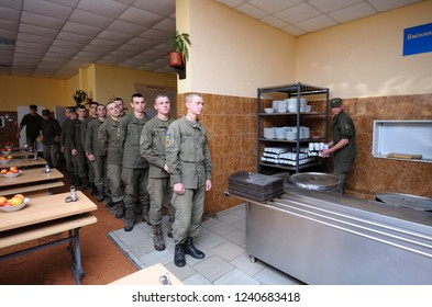 Editorial use only. At a chow hall: soldiers stand in front of a serving bar and wait for kitchen worker preparing meal for distribution. November 12, 2018. Novo-Petrivtsi military base, Ukraine