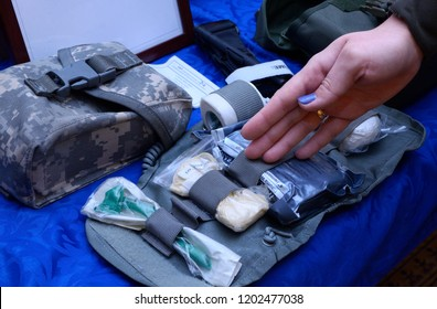 Editorial use only. Woman's hand showing content of an Ukrainian soldier's first aid kit: bandages, wound-healing drugs, tourniquet, painkillers. October 7, 2018. Kiev, Ukraine