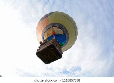 """Editorial use only. Hot-air balloon drifting in the sky, people looking out from a basket, view from below. Festival of balloons """"Pereiaslav-2018"""". May 6, 2018. Pereiaslav, Ukraine"""