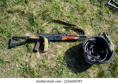 Editorial use only. Kalashnikov assault rifle and soldier's helmet laying on a ground. October 18, 2018. Novo-Petrivtsi military base, Ukraine