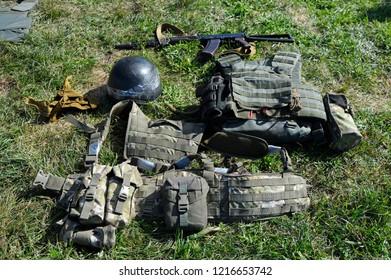Editorial use only. Kalashnikov assault rifle, soldier's helmets and bulletproofs laying on a ground. October 18, 2018. Novo-Petrivtsi military base, Ukraine