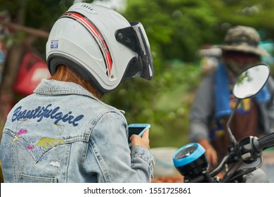 Editorial use only; a lady on a motorcycle wearing a crash helmet, is checking her phone, taken at Pathumthani, Thailand, in August 2019.