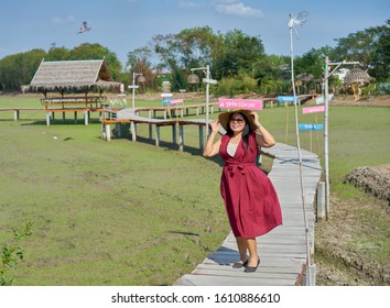 Editorial use only; a lady walks on a wooden walkway through a rice field, taken at Pathumthani, Thailand, in January 2020.