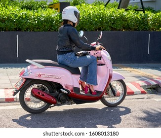 Editorial use only; a lady wearing a helmet, riding on a pink scooter, taken atPattaya, Thailand, in January 2020.