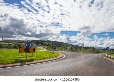 Editorial use only; a large bend on a road, with a very white clouds sky, taken outside Cashel, Co. Tipperary, Ireland, in September, 2018.