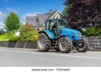 Editorial use only; large blue tractor on a rural road, taken outside Mohill, Co. Leitrim, Ireland, on July 27th, 2017.