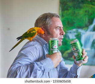 Editorial use only; a man drinking beer while a small bird whispers in his ear, taken at Pathumthani, Thailand, in October 2019.