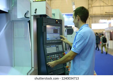 Editorial use only. Man in work clothes stands in front of a control panel of a milling machine preparing it for work. 17-th Industrial Exhibition. Kiev, Ukraine. November 23, 2018