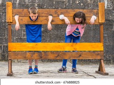 Editorial use only; naughty kids in medieval stocks, punishment concept, taken at Athlone castle on July, 12th, 2017.