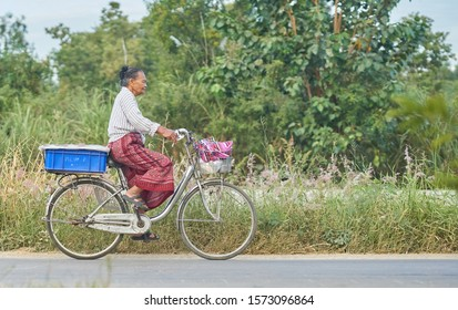 Editorial use only; an old lady riding a bicycle in a rural setting, taken at Pathumthani, Thailand, in November 2019.
