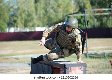 Editorial use only. On a military training ground, obstacle course: Ukrainian soldier jumping over a barrier. October 18, 2018. Novo-Petrivtsi military base, Ukraine